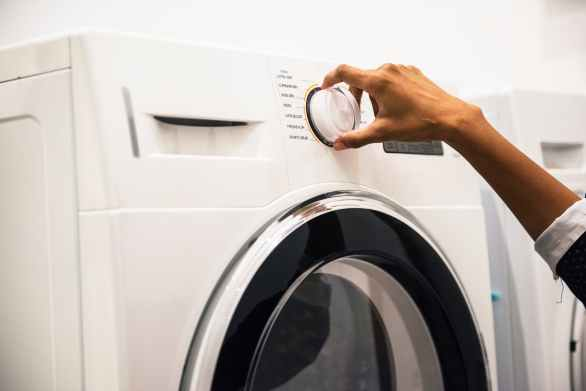 person adjusting control on front load clothes washer